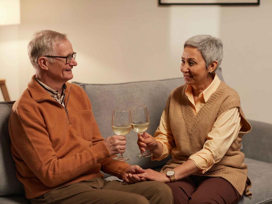 Senioren auf einer Couch prosten sich mit einem Weinglas zu.